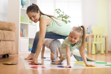 Young mom playing twister game with her children daughters. Happy family have a fun time in holiday
