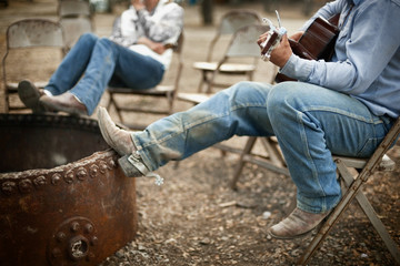 Man plays guitar as he and a male friend relax resting their spurred cowboy boots on the edge of an empty outdoor metal firepit.