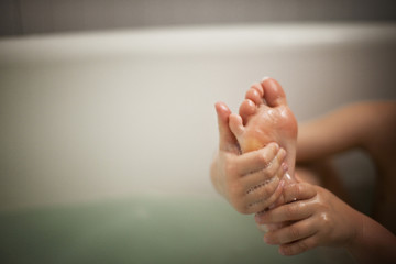 A boy's wet hands and feet as he takes a bath