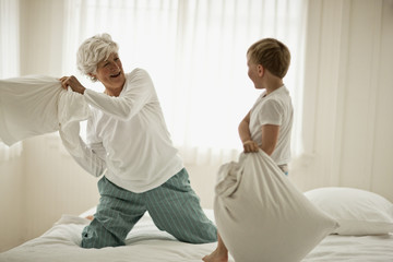 Mature woman and a young boy have a pillow fight on a bed.