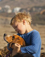 Young boy sits on the beach playing with his dog.