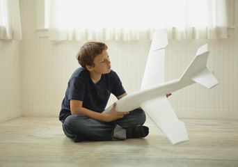 Preteen boy daydreaming as he holds a model airplane.