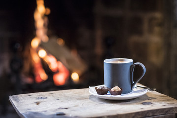 Close up of mug with hot drink on wooden table in front of fireplace.