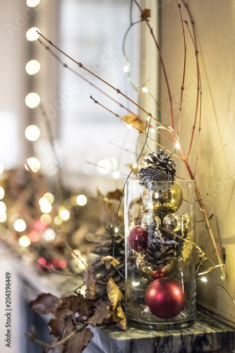 Close up of red and golden Christmas decorations in a vase, bauble, leaves and