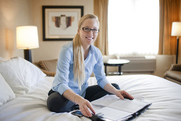 Young businesswoman with a personal organiser open in front of her smiles and poses for a portrait as she sits cross-legged on a bed in a hotel room during a business trip.