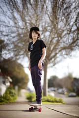 Teenage boy skateboarding along a street.