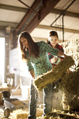 Two young women lifting hay bales in a barn.