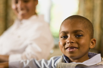 Young boy smiles as he poses for a portrait while sitting at a table with a woman in the background.