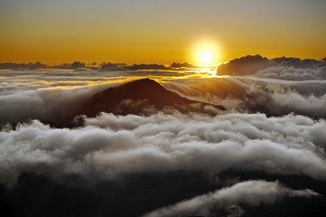 Silhouette of mountains surrounded by a sea of clouds at sunset.