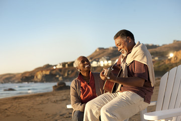 Smiling senior woman listening to her husband play an acoustic guitar on a beach.