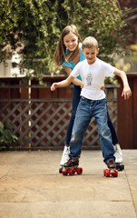 Girl holding onto her younger brother's waist as they try to roller skate.
