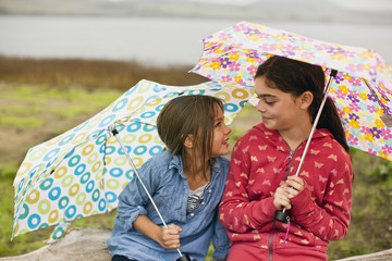 Two young girls smile and talk as they sit together on a fallen tree trunk while holding open umbrellas.