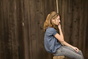 A lonely teenage girl swinging on a rope swing in her back yard.