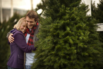 Happy couple sharing a moment at a Christmas tree farm.