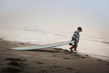Little boy dragging surfboard into the sea.