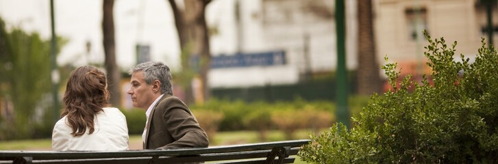 Serious man listens to a woman as they sit together on a park bench.