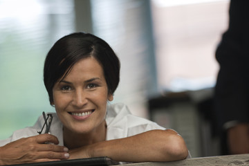 Businesswoman holds a pair of eyeglasses and smiles as she poses for a portrait.