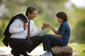 Businessman father crouches down to knock fists together (daps) with his young son who sits on a rock in a park.