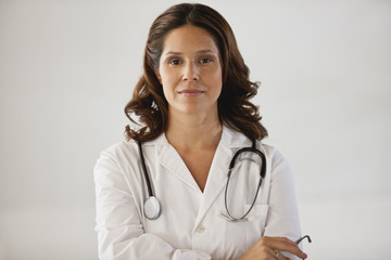 Thirtysomething female doctor wearing white coat and stethoscope poses for a portrait.
