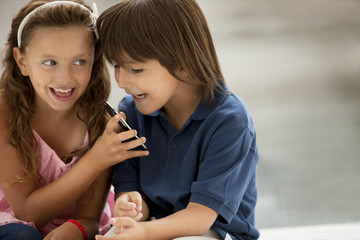 A young boy and girl smile mischievously as they look at a cellphone.