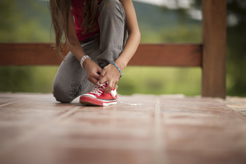 Girl wearing high top sneakers ties her shoe laces.