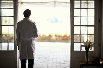 Male doctor standing at doorway,  looking out over courtyard.