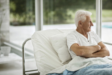 Portrait of senior male patient in a hospital bed.