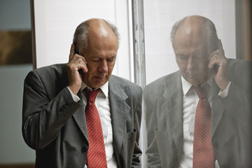 Senior businessman on a stressful phone call.