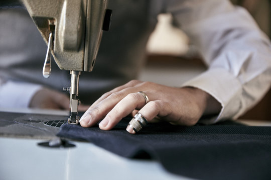 Man using industrial sewing machine to stitch garment