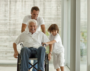 Senior man being pushed in wheelchair,  by his adult son and his grandson.