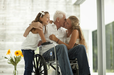 Senior man in wheelchair,  greeting his granddaughters.