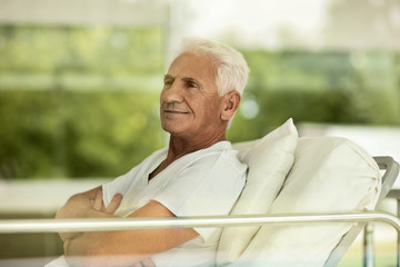 Portrait of senior male patient in a hospital bed looking reflective.