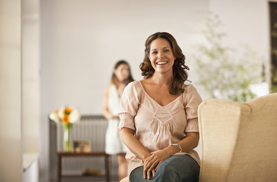 Portrait of mid adult woman at home, with her daughter in the background behind her.