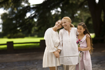 Grandmother, daughter, and granddaughter stand together outdoors at a park.