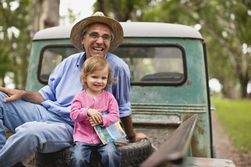Portrait of mature man and his toddler granddaughter sitting in the back of truck.