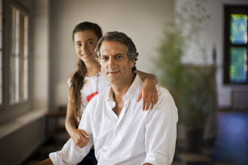 Portrait of girl standing with arm around her father.