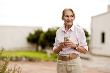 Woman holding a sprig of vegetation.