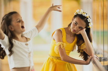 Girl sulking as she watches her sister dance.