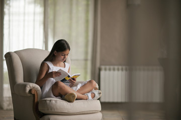 Young girl reading on armchair.