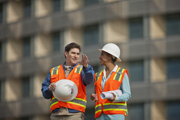 Two engineers in high visibility vests and hardhats discuss building plans on a construction site.