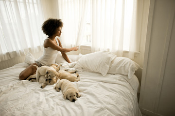 Woman sitting on bed looking out window with a group of puppies.
