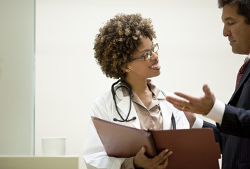 Male and female doctor discussing patient files.