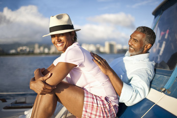 Mature couple lying back, relaxing on boat.