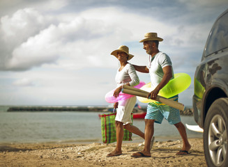 Couple walking to the beach with swim rings and beach mats.