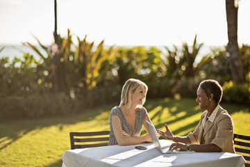 Two business colleagues sitting at outside table on lawn, for meeting.