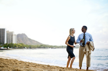 Two business partners enjoy walking on the beach together.