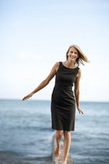Happy businesswoman walking by the sea with arms outstretched.