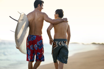 Surfer walking on the beach with his younger brother.