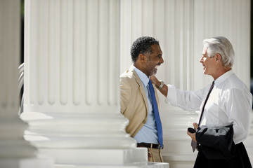 Two adult businessmen having a discussion on a porch.
