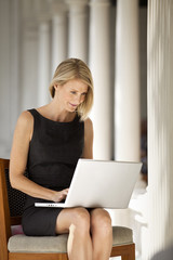 Mid-adult woman using a laptop while sitting on a porch.